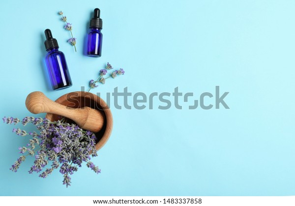 Bottles of essential oil, mortar and pestle with lavender flowers on light blue background, flat lay. Space for text