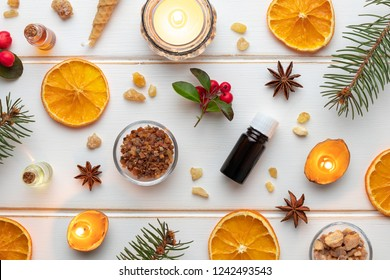 Bottles of essential oil on a white Christmas background with frankincense, myrrh, dried orange slices and candles made from nut shells