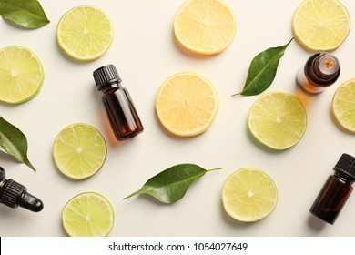 Bottles of essential oils and citrus slices on light background, top view