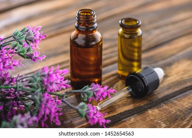 bottles with essential oils, dropper and heather plant on wooden surface
