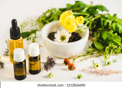 bottles of essential oils and herbs on white surface, alternative medicine concept