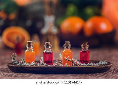 Bottles filled with red and orange essential oils on wooden board. Fresh citrus fruit cut in half. Aromatherapy relax concept