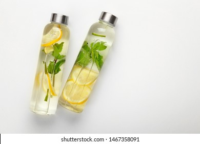 Bottles of fresh infused water on white background