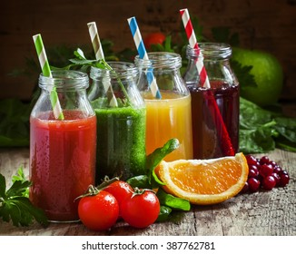 Bottles with fresh juices from fruits and vegetables on an old wooden background, selective focus