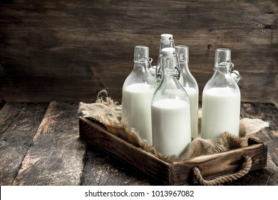 Bottles with fresh milk in a box. On a wooden background.