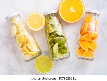 Bottles of fresh summer water with oranges with limes and lemons slices on marble background with fresh fruits