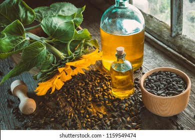 Bottles of fresh sunflower oil, wooden mortar of seeds and yellow sunflower on wooden table inside the retro village house.