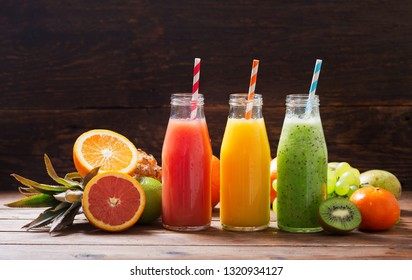 bottles of fruit juice and smoothie with fresh fruits on wooden table
