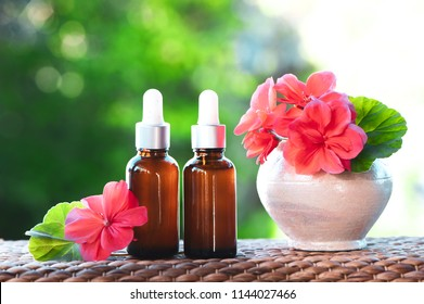 Bottles with geranium oil, fresh flower and leaves on a natural green background,  bio, organic , nature cosmetics concept