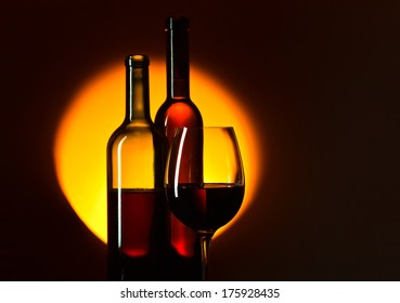 bottles and glass with red wine on dark background