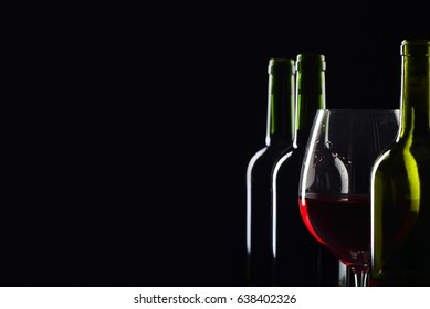 Bottles and glass of red wine on a black background . Selective focus .
