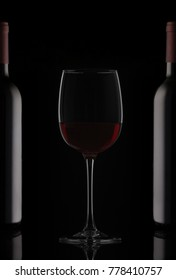 Bottles and glass of red wine with reflection on black background as horizontal seamless