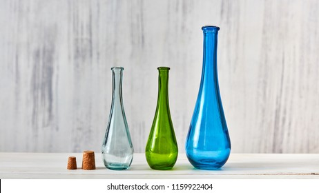 The bottles green, blue, transparent stand on a gray table on a light gray background with place for text. Concept of saving homemade products.