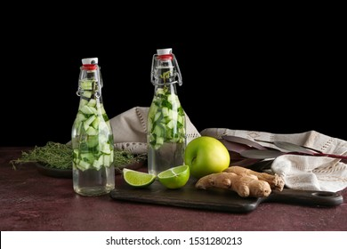 Bottles of healthy infused water with ingredients on table