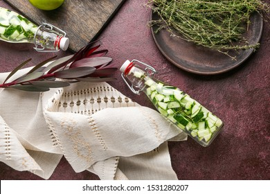 Bottles of healthy infused water with thyme on table