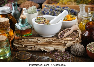 Bottles of healthy infusion or oil, mortars and bowls of medicinal herb, old book. Herbal medicine.