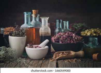 Bottles of healthy tincture or infusion, mortar and bowls of medicinal herbs on wooden table. Herbal medicine.
