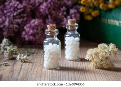 Bottles of homeopathic globules with dried herbs and a materia medica, i.e. a book of remedies and their therapeutic properties, in the background