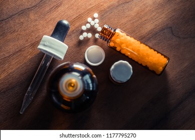 Bottles of homeopathic globules and dropper on wooden table. Homeopathy medicine