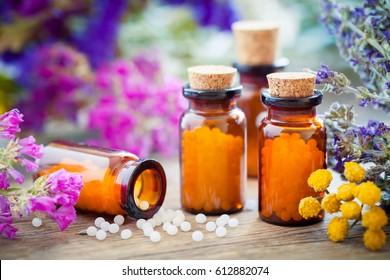 Bottles of homeopathic globules and healing herbs and flowers. Homeopathy medicine.