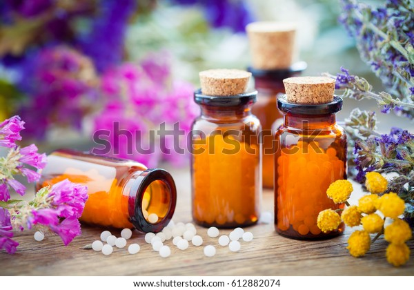 Garrafas de glóbulos homeopáticos e ervas curativas e flores. Remédio para homeopatia.