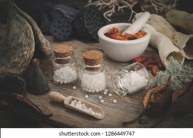Bottles of homeopathic globules, mortar of dried chili pepper, dry roots, nuts and plants. Homeopathy medicine.
