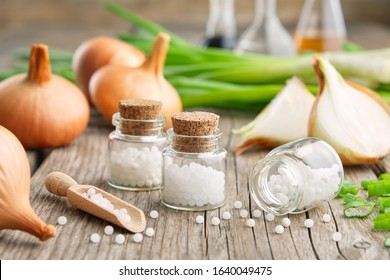 Bottles of homeopathic globules, onion bulbs and fresh green onions. Allium cepa homeopathic remedies.