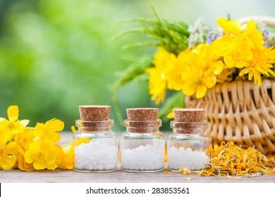 Bottles of homeopathy globules and healthy herbs in wicker basket.
