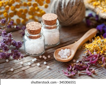 Bottles of homeopathy globules, wooden spoon and dry healthy herbs. Selective focus.