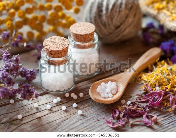 Bouteilles de globules homéopathiques, cuillère en bois et herbes sèches saines. Mise au point sélective.