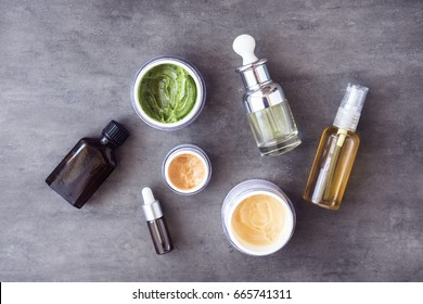 Bottles and jars with natural skincare cosmetics, creams and oils on dark background. Plant-based beauty products. Top view