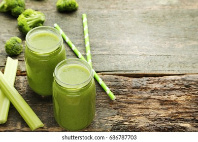 Bottles of juice with broccoli and celery on grey wooden table