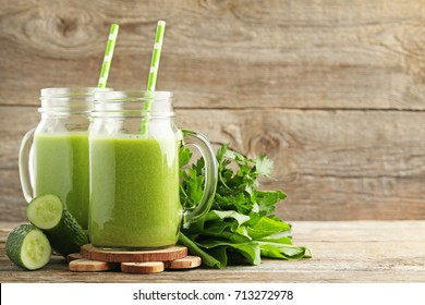 Bottles of juice with cucumber and parsley on grey wooden table