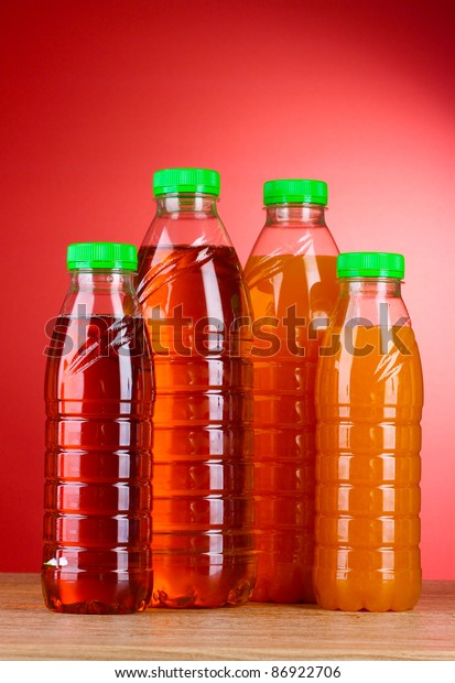 Bottles with juice on red background