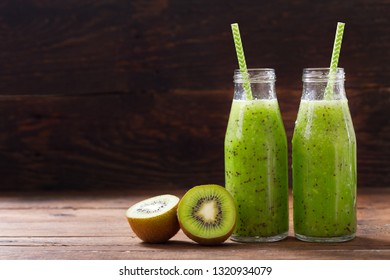 bottles of kiwi juice or smoothie with fresh fruits on wooden table
