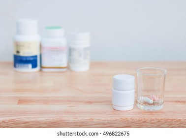 Bottles of medicine capsules and pills in small glass on wooden floor. With copy space.