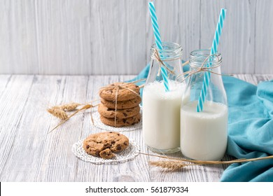 Bottles of milk with blue straws and chocolate chip cookies on wooden background