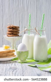 Bottles of milk with straws, boiled egg, toasts with butter and cookies, wooden background, healthy breakfast concept