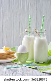Bottles of milk with straws, boiled egg and toasts with butter, wooden background, healthy breakfast concept
