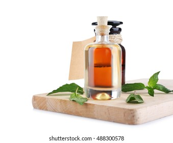Bottles of mint oil and fresh leaves on wooden board on white background