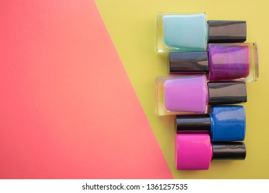 Bottles of nail polish. A group of bright manicures on a pink, yellow background. With empty space on the left. View from above