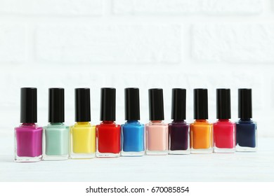 Bottles of nail polish on brick wall background