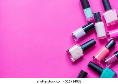 lot of bottles nail polish on pink background top view