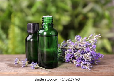 Bottles with natural lavender essential oil on wooden table against blurred background