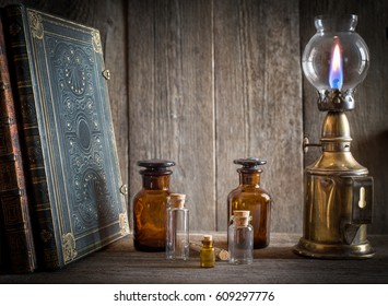 Bottles, old book and lamp on the shelf in old pharmacy.