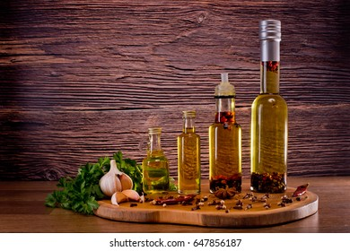 Bottles with olive oil with spices on a wooden background, cloves of garlic and parsley. Backgrounds for the kitchen.