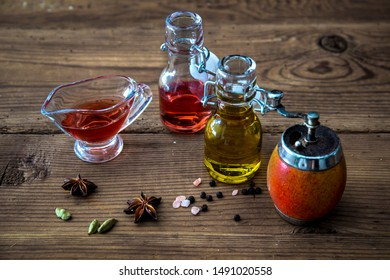bottles with olive oil and vinegar, kitchen grinder and spices on wooden background