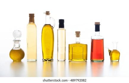 Bottles of olive oil and vinegar on white background