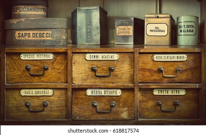 Bottles on the shelf in old pharmacy. The labels on bottles and a shelf  inscription in Latin language. Translation: gum Arabic, chalk white, turmeric root, thoracic collecting, soap, mustard, cocoa.