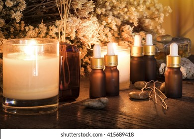 Bottles with organic essential aroma oil with dry flower on old wooden background.